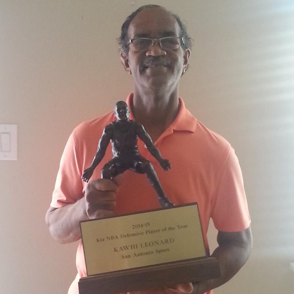 Kawhi Leonard's girlfriend Kishele Shipley's father posing with Leonard's MVP award.
